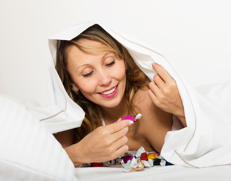 lier: Happiness woman eating chocolate candy and smiling  in bed Stock Photo