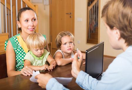 delincuencia: Madre feliz con dos peque�os hijos palabras auditivos alegres de trabajador social en el hogar