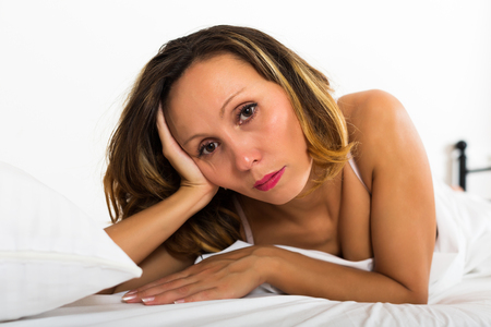 unbearable: Portrait of thoughtful woman with downcast eyes in bedroom Stock Photo
