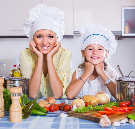 vegeterian: smiling mom and little daughter cooking vegeterian dish indoors