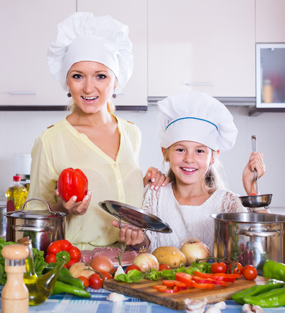 vegeterian: smiling spanish mom and little daughter cooking vegeterian dish indoors