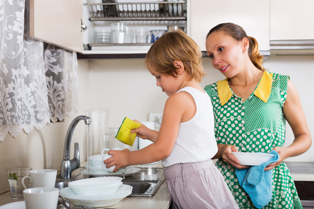 one parent: Baby girl  with woman washing dishes in kitchen