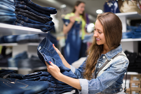 ordinary woman: Joyful smiling young longhaired girl choosing new jeans at store Stock Photo