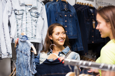 coatee: Two young happy girls buying denim vest in clothing store