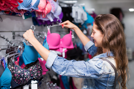 brassiere: Young attractive woman buying brassiere in clothing store Stock Photo