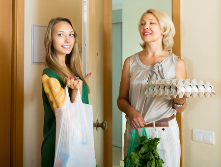 foodstuff: Two european female friends returning home after foodstuff shopping
