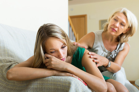 home comforts: Mature mother gives solace to crying adult daughter at home.  Focus on young