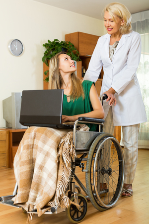 incapacitated: Happy woman in wheelchair with working on laptop at home