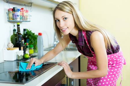 stay home work: Happy young woman cleans modern stove cleaner at his home Stock Photo