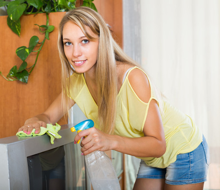 cleanser: Blonde young woman cleaning TV with cleanser at home