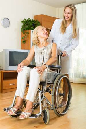medical assistant: Smiling woman in wheelchair with medical assistant in room Stock Photo