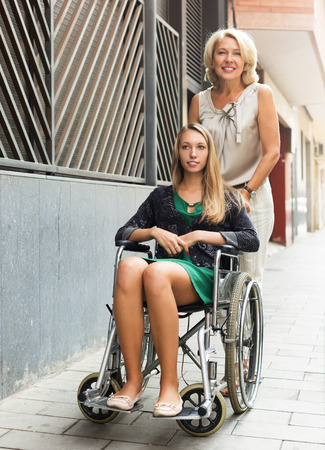 incapacitated: Smiling female helping handicapped woman on the street