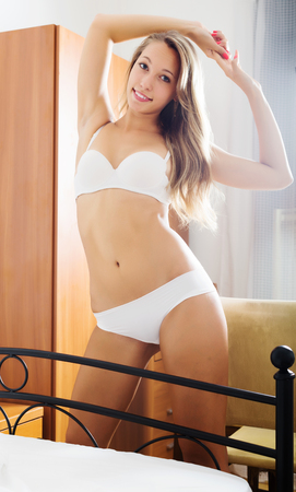stretchy: Cheerful long-haired  woman in underwear stretching  in bedroon