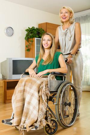 paraplegic: Sonriendo ancianos médico visitando joven discapacitado en el hogar