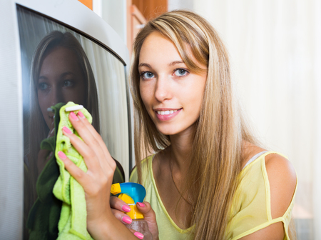 televisor: Smiling blonde young woman cleaning TV with cleanser at home