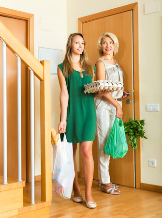 foodstuff: mother and daughter coming home after foodstuff shopping Stock Photo