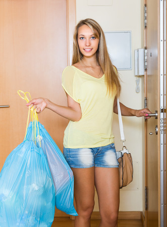 ordinary: Ordinary young woman staying at the door with trash bags
