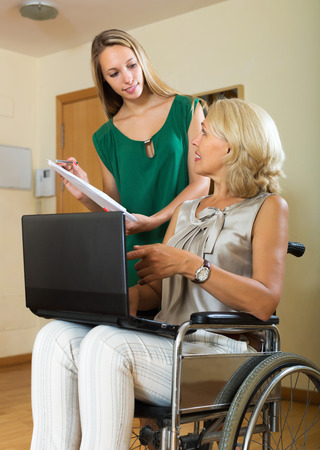 incapacitated: Friendly insurance agent and mature disabled female on chair indoor