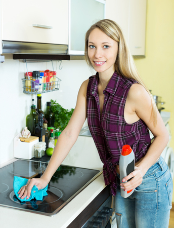 stay home work: Cheerful young maid cleans modern stove cleaner at home