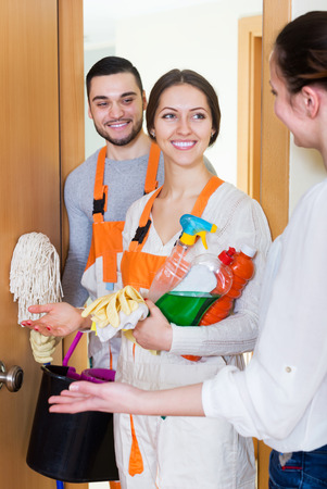 houseman: Professional happy young cleaners with equipment standing at doors of client house