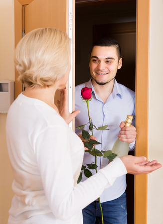 Mature woman meeting young handsome guy with flowers and wine in hands at doorway