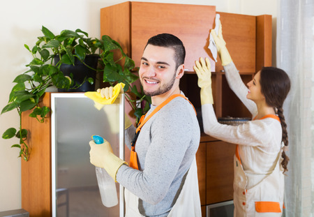 houseman: Smiling rofessional cleaners with equipment clean furniture of client house