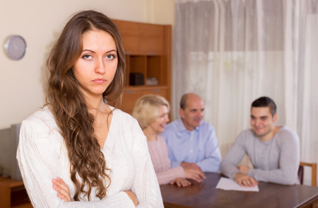 staying: Upset girl staying against united family members Stock Photo