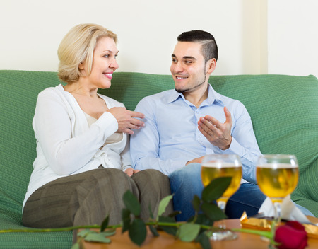 Happy smiling senior woman with young boyfriend drinking wine at home