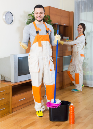 company premises: Portrait of positive professional cleaners with equipment working at client house