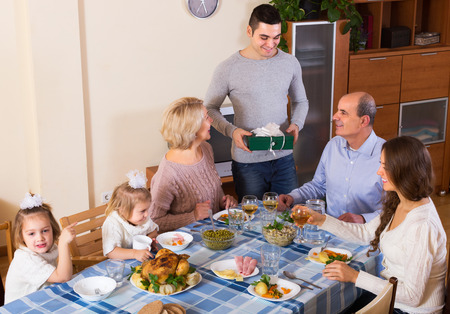 home family: Smiling family member receiving present from relatives