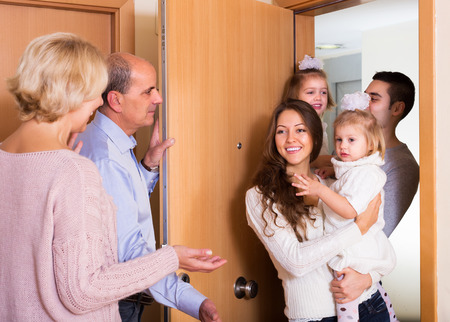granny and grandad: Friendly senior people welcoming dear guests with kids indoor