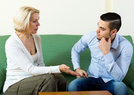 dialogo: Atractivo hombre y su novia madura que tiene una conversación seria en el interior