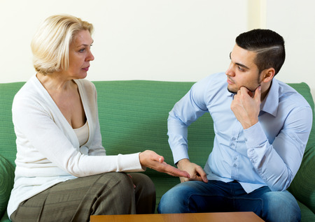 Attractive man and his mature girlfriend having serious conversation indoors Stock Photo