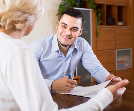mismatch: Smiling adult son helping mature mother with financial documents at the table