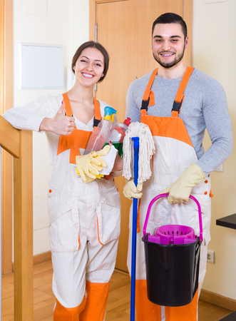 company premises: Portrait of professional cleaners team with equipment at the doors of client house Stock Photo