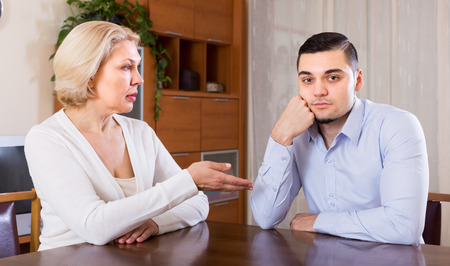 adult intercourse: Aged woman and young boyfriend discussing something with serious faces at home