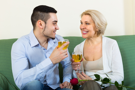 congratulating: Adult son congratulating smiling senior mother and proposing a toast. Focus on woman