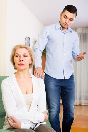 mismatch: Quarrel between adult son and senior mother in the living room at home Stock Photo