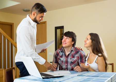 sales promotion: Young happy salesman try hard to sign a finance contract with merried couple
