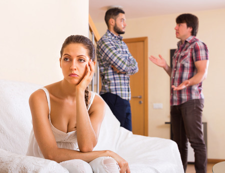 mistrust: Three unhappy adults having argue at home interior Stock Photo