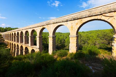 aqueduct: ancient roman aqueduct in summer forest. Tarragona,  Spain Stock Photo