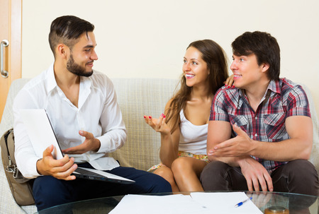 cheerfully: Smiling young couple and positive salesman talking cheerfully about purchase at home