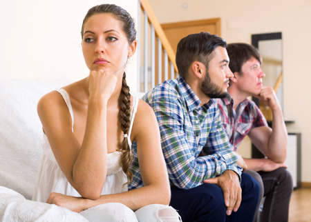 polygamy: Two adult men quarreling over a woman at home Stock Photo