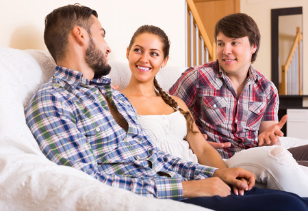 bisexual women: Portrait of young smiling polygamous family posing at home Stock Photo