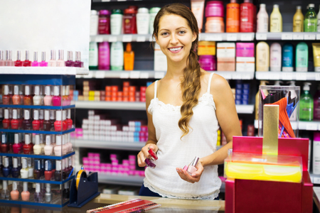 store clerk: Smiling store clerk with nail polish at cash desk in the shopping mall Stock Photo