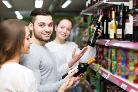 two women and one man: One man and two women choosing red wine in a liquor store