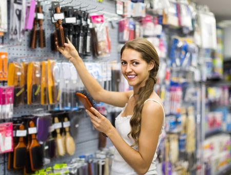 beauty shop: Young american girl buying hairbrush in shopping mall