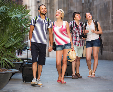 tourists: Company of young travelers with travel bags walking the city