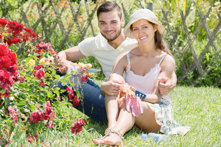 floriculturist: Cheerful married couple  resting at the flowers garden