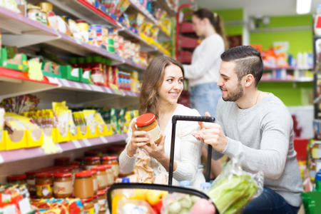 canned goods: smiling customers standing near shelves with canned goods at shop Stock Photo